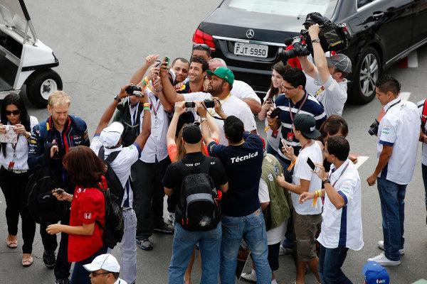 Interlagos, Sao Paulo, Brazil. Sunday 9 November 2014. Daniel Ricciardo, Red Bull Racing, poses for photos with fans. World Copyright: Charles Coates/LAT Photographic. ref: Digital Image _J5R5397