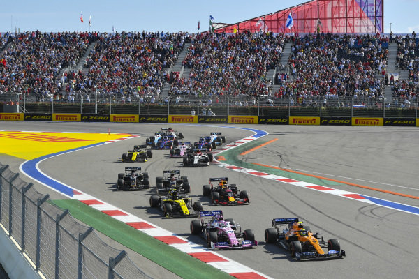 Lando Norris, McLaren MCL34, leads Sergio Perez, Racing Point RP19, Nico Hulkenberg, Renault R.S. 19, Max Verstappen, Red Bull Racing RB15, Kevin Magnussen, Haas VF-19, Romain Grosjean, Haas VF-19, and the remainder of the field at the start