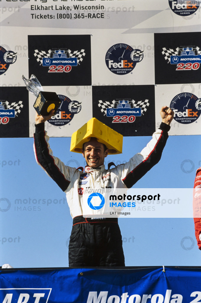 Cristiano da Matta, 1st position, wears a hat styled to look like a block of cheese on the podium.