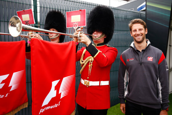 Silverstone, Northamptonshire, UK.  Sunday 16 July 2017. Romain Grosjean, Haas F1, poses with some trumpeters in Scots Guard uniforms. World Copyright: Andy Hone/LAT Images  ref: Digital Image _ONZ6213