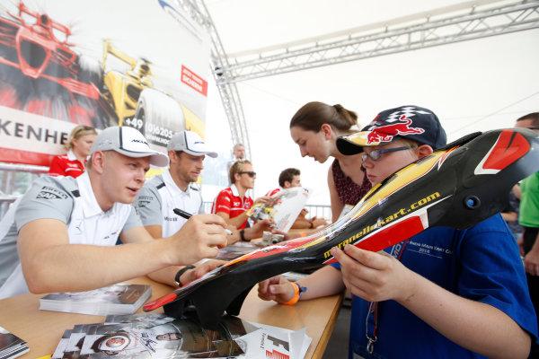 Hockenheimring, Hockenheim, Germany. Saturday 19 July 2014. Kevin Magnussen, McLaren, and Jenson Button, McLaren, sign autographs for fans. World Copyright: Charles Coates/LAT Photographic. ref: Digital Image _N7T4181