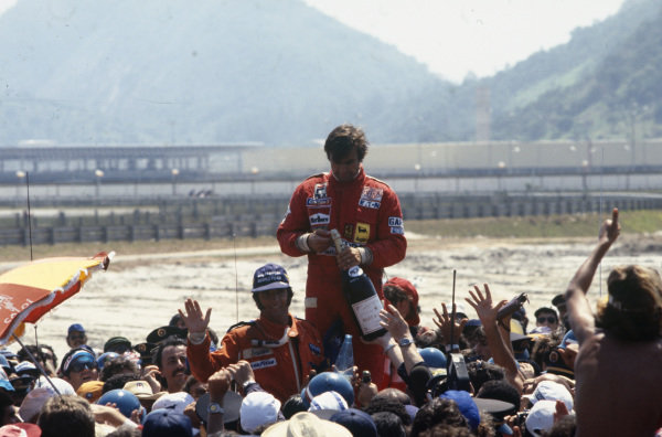 Carlos Reutemann celebrates victory on the podium with Emerson Fittipaldi, 2nd position.