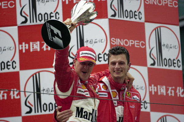 Michael Schumacher brandishes his trophy to the team with race engineer Chris Dyer.