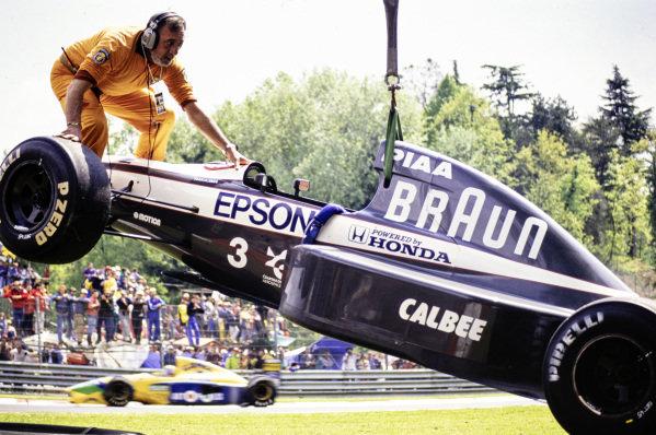 Satoru Nakajima's Tyrrell 020 Honda is recovered by crane.