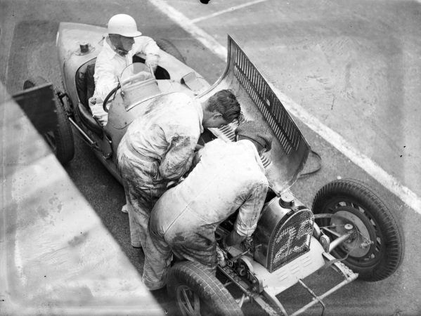 Mechanics work on the engine in a Bugatti in the pits while the driver sits in the car.