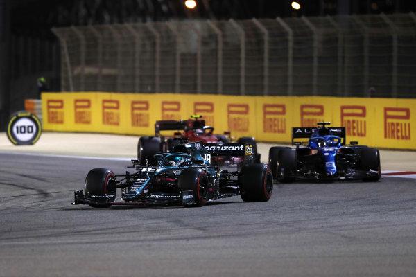 Lance Stroll, Aston Martin AMR21, leads Fernando Alonso, Alpine A521, and Carlos Sainz, Ferrari SF21