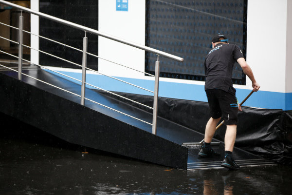 Williams Racing team member removing water from the motorhome entrance