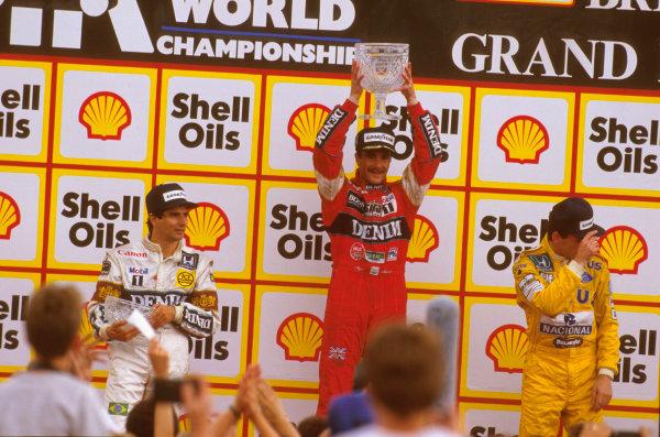 Silverstone, England.10-12 July 1987.Nigel Mansell (Williams Honda) 1st position, Nelson Piquet (Williams Honda) and Ayrton Senna (Lotus Honda) 3rd position on the podium.Ref-87 GB 15.World Copyright - LAT Photographic