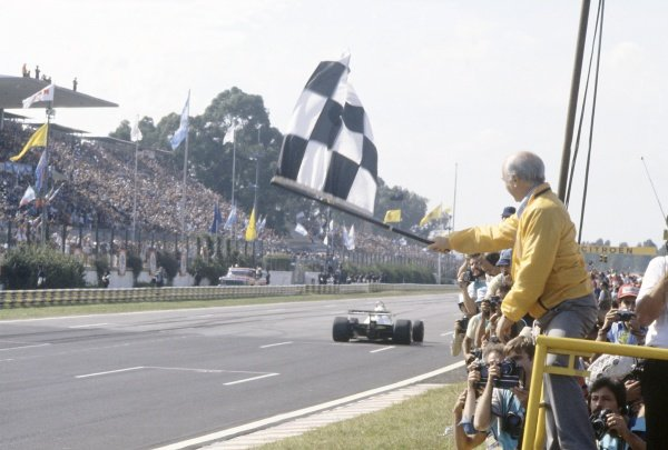 1981 Argentinian Grand Prix.Buenos Aires, Argentina. 10-12 April 1981.Juan Manuel Fangio shows the chequered flag to Carlos Reutemann (Williams FW07C-Ford Cosworth), 2nd position.World Copyright: LAT PhotographicRef: 35mm transparency 81ARG02