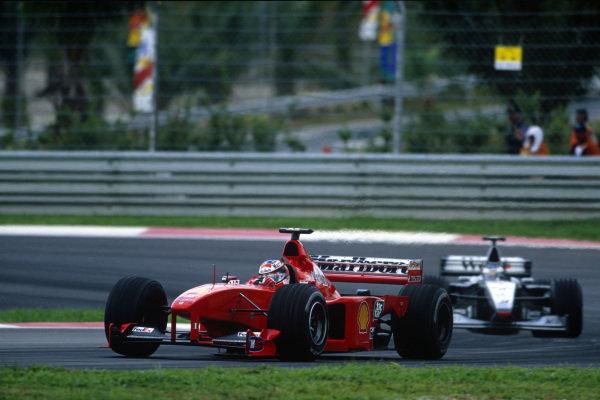 Sepang, Kuala Lumpur, Malaysia. 15-17 October 1999. Michael Schumacher (Ferrari F399) holds up Mika Hakkinen (McLaren MP4/14 Mercedes) alowing team mate Eddie Irvine to build a lead. Ref: 99MAL05. World Copyright - LAT Photographic