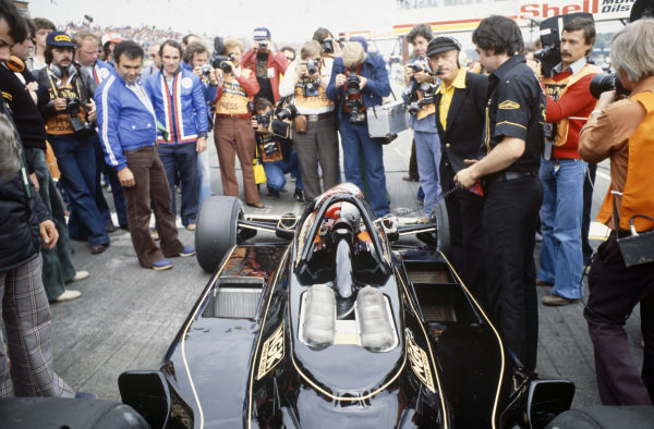 Photographers take pictures of Mario Andretti on the grid in his Lotus 79 Ford.