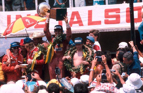 1977 Brazilian Grand Prix.Interlagos, Sao Paulo, Brazil.21-23 January 1977.Carlos Reutemann (Ferrari) 1st position, James Hunt (McLaren Ford) 2nd position and Niki Lauda (Ferrari) 3rd position on the podium. Hunt has a chat with Emerson Fittipaldi.Ref-77 BRA 05.World Copyright - LAT Photographic
