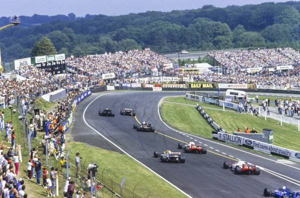 Nelson Piquet, Williams FW11 Honda, leads Ayrton Senna, Lotus 98T Renault, Gerhard Berger, Benetton B186 BMW, Alain Prost, McLaren MP4-2C TAG, and Nigel Mansell, Williams FW11 Honda, into Paddock Hill Bend at the start.