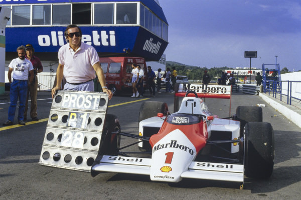 """Jackie Stewart's long-standing record of 27 grand prix wins was beaten by Alain Prost in Portugal. Here, Stewart stands alongside a pit board with """"PROST, P1, 28"""" signage on it, and Prost's McLaren MP4-3 TAG."""