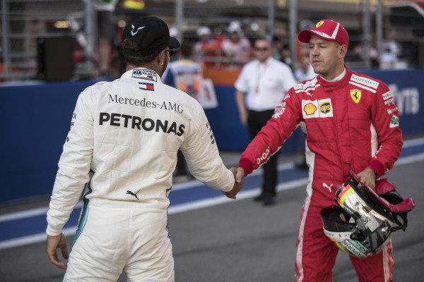 Lewis Hamilton, Mercedes AMG F1, shakes Sebastian Vettel, Ferrari, hand after qualifying.