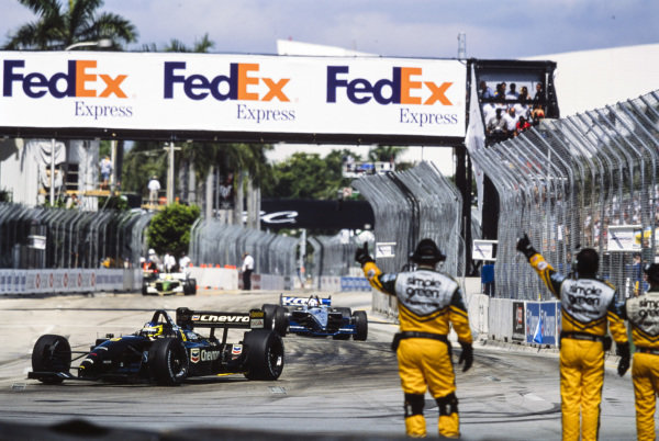 Cristiano da Matta, Newman/Haas Racing, Lola B02/00 Toyota, leads Dario Franchitti, Team Green, Lola B02/00 Honda, past the safety team who give the drivers a thumbs up.