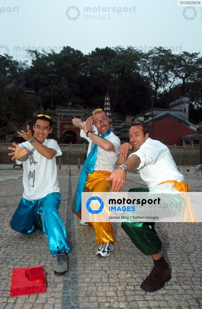 Winner of the Macau GP, Takuma Sato (JPN), left, strikes a martial arts pose with touring car driver Tom Coronel (NED), right.