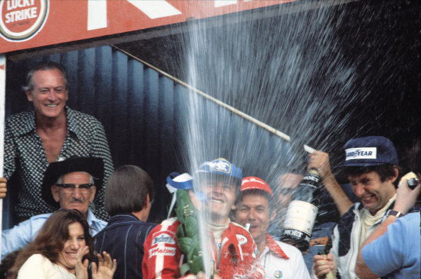 Kyalami, South Africa. 1 - 3 March 1979.Gilles Villeneuve (Ferrari 312T4), 1st position, celebrates on the podium with Jean Pierre Jarier (Tyrrell 009-Ford), 3rd position, portrait. World Copyright: LAT Photographic.Ref: 79SA21