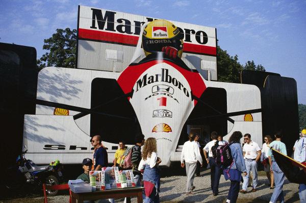 A large billboard depicting Ayrton Senna's McLaren MP4-7A Honda in the paddock.
