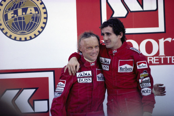 Alain Prost, 1st position, and Niki Lauda, 2nd position and World Champion, celebrate on the podium.