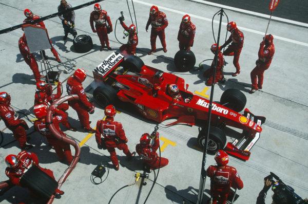 Sepang, Kuala Lumpur, Malaysia. 15-17 October 1999. Michael Schumacher (Ferrari F399) pulls away from a pitstop. Action. Ref: 99MAL11. World Copyright - LAT Photographic