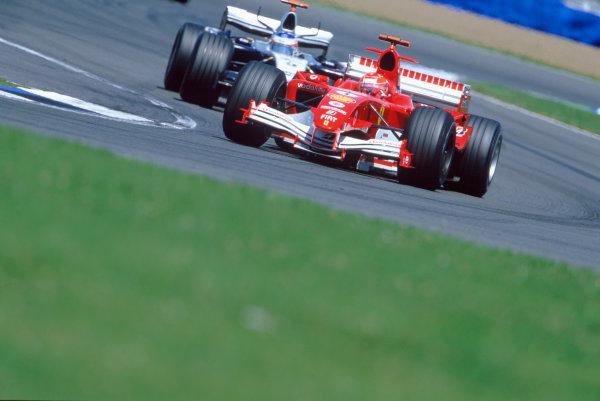 2005 British Grand Prix. Silverstone, England. 8th - 10th July 2005 Michael Schumacher, Ferrari F2005 leads Kimi Raikkonen, McLaren Mercedes MP4-20. Action. World Copyright: Lorenzo Bellanca/LAT Photographic Ref: 35mm Image A13