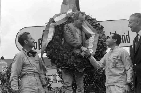 John Surtees, 1st position, celebrates on the podium, with Graham Hill, 2nd position, and Lorenzo Bandini, 3rd position.