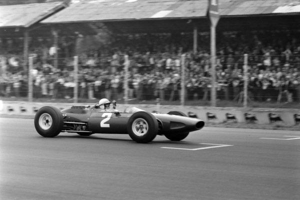 John Surtees, Ferrari 158, raises a fist in celebration.