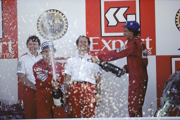 Alain Prost celebrates winning the race and Niki Lauda celebrates winning the World Championship by half a point from Prost, alongside John Barnard and Ron Dennis on the podium