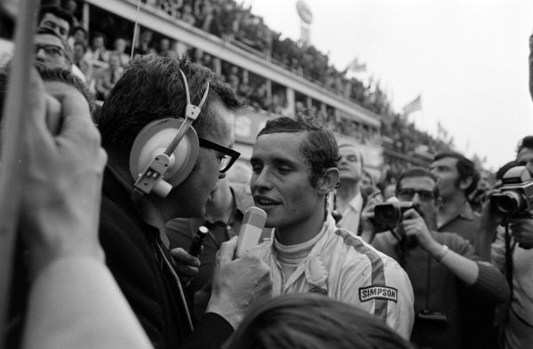Jacky Ickx is interviewed on his way to the podium.