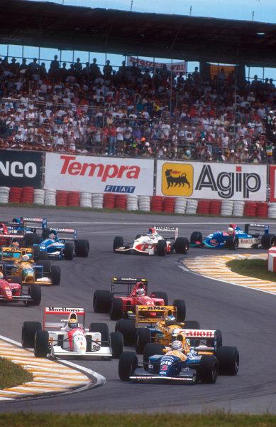 1992 Brazilian Grand Prix.Interlagos, Sao Paulo, Brazil.3-5 April 1992.Nigel Mansell (Williams FW14B Renault) followed by Ayrton Senna (McLaren MP4/7A Honda), Michael Schumacher (Benetton B191B Ford) and Jean Alesi (Ferrari F92A) at the start.Ref-92 BRA 08.World Copyright - LAT Photographic