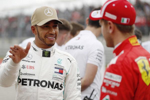 Lewis Hamilton, Mercedes AMG F1, talks with Sebastian Vettel, Ferrari, after taking Pole Position