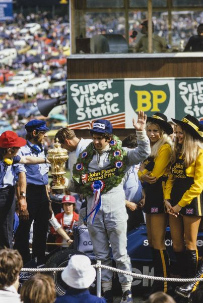 Jody Scheckter celebrates victory on a trailer carrying his Tyrrell 007, mechanic Roy Topp and JPS promotional girls.