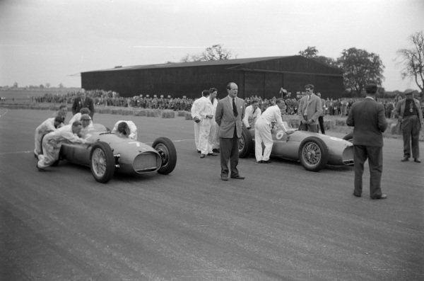 Peter Walker, BRM P15, and Reg Parnell, BRM P15, take up position on the grid.