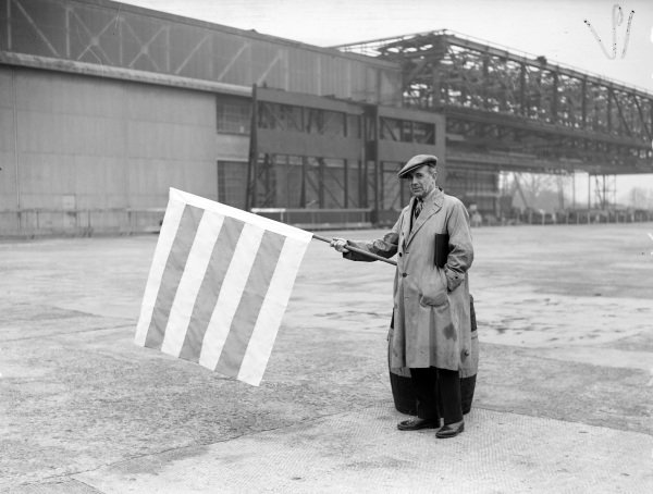 Earl Howe displays the red and yellow flag to warn drivers of oil on the track. This was the first time this flag had been used at Brooklands.