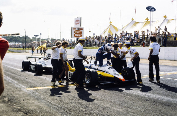 Winner Alain Prost, Renault RE30B, steps out of his car and is greeted by his team after the race, with second-placed Carlos Reutemann, Williams FW07D Ford, behind.