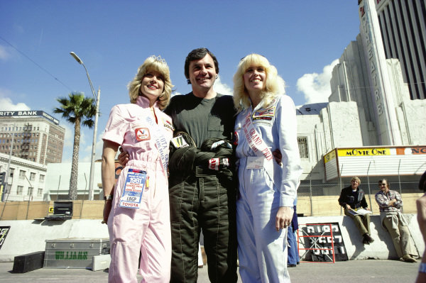 Alan Jones with two 'Miss Toyota Grand Prix'.