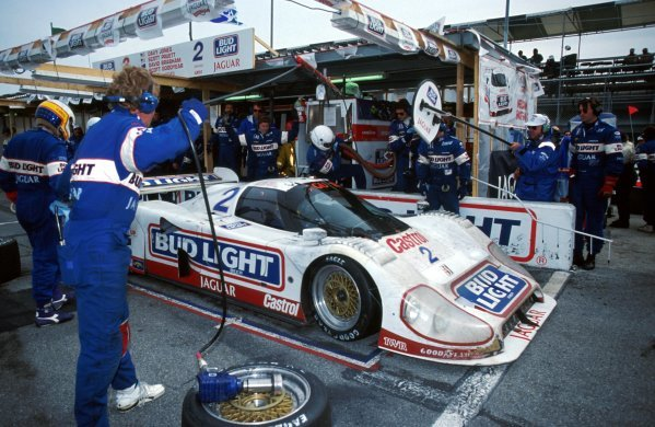Davy Jones (USA) left, waits for his team mate to leave the pits in the TWR Jaguar XJR-12D after a pitstop.