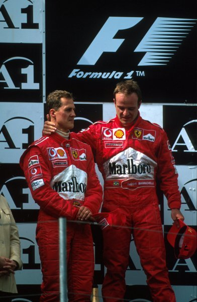 Michael Schumacher (GER) and Rubens Barrichello (BRA) find themselves unsure how to react on the podium after the contrived finish forced upon them by the Ferrari team management.Formula One World Championship, Rd6, Austrian Grand Prix, A1-Ring, Austria. 12 May 2002.BEST IMAGE