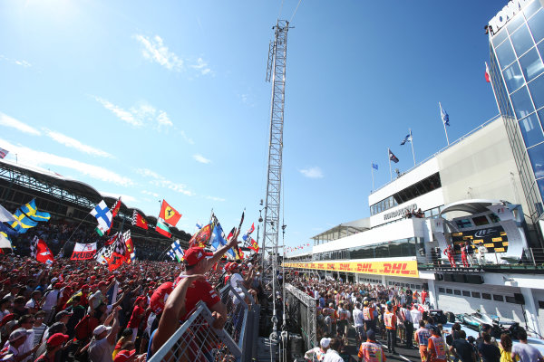 Hungaroring, Budapest, Hungary.  Sunday 30 July 2017. Fans cheer for Sebastian Vettel, Ferrari, 1st Position, Kimi Raikkonen, Ferrari, 2nd Position, and Valtteri Bottas, Mercedes AMG, 3rd Position, on the podium. World Copyright: Charles Coates}/LAT Images  ref: Digital Image AN7T9833