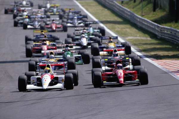 Ayrton Senna, McLaren MP4-6 Honda, and Alain Prost, Ferrari 643, lead the field into the first corner at the start.