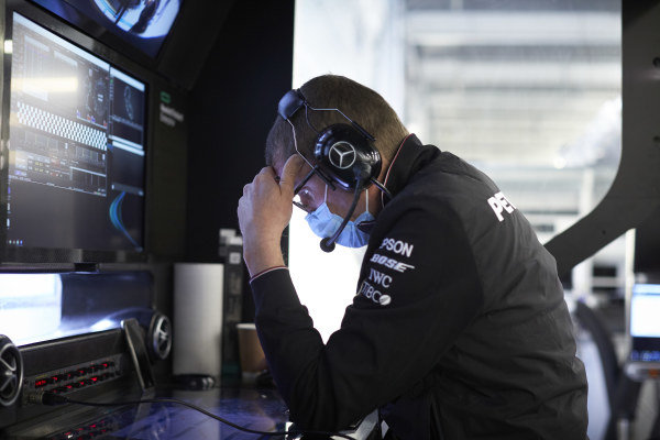 Mercedes AMG F1 team members wear protective masks in the garage.