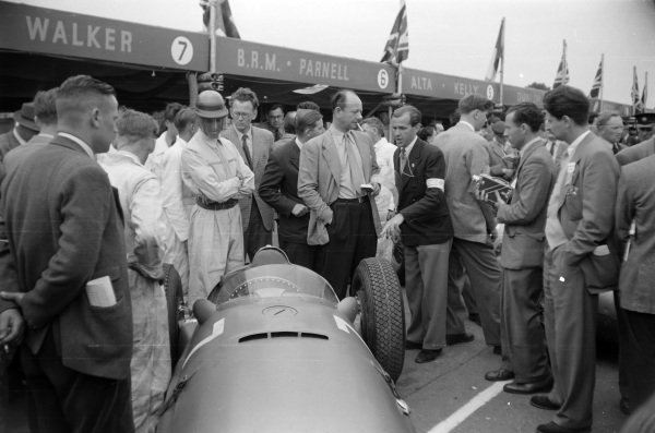 Peter Walker stands behind his BRM P15 in the pits, with Raymond Mays on the right.