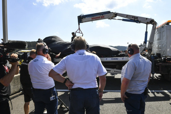 The damaged Lewis Hamilton Mercedes AMG F1 W10 returns to the pits on a the back of a truck in FP3. FIA officials watch on