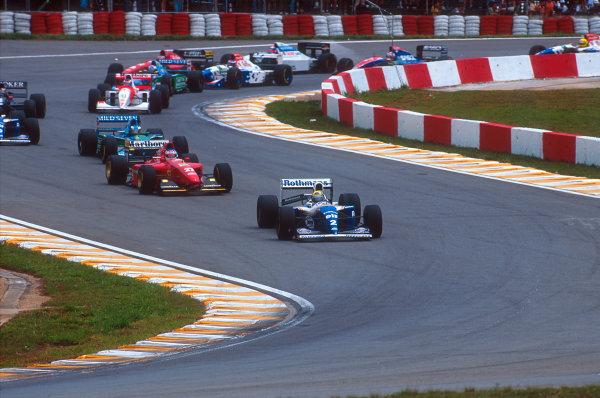 Interlagos, Sao Paulo, Brazil.25-27 March 1994.Ayrton Senna (Williams FW16 Renault) leads Jean Alesi (Ferrari 412T1) and Michael Schumacher (Benetton B194 Ford)) at the start.Ref-94 BRA 11.World Copyright - LAT Photographic