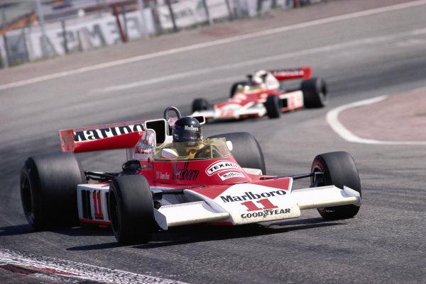 James Hunt, McLaren M23 Ford, leads his team-mate Jochen Mass.