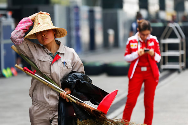 Shanghai International Circuit, Shanghai, China. Thursday 14 April 2016. A worker at the Shanghai Circuit is pictured in front of a Ferrari team member. World Copyright: Andy Hone/LAT Photographic ref: Digital Image _ONY2985