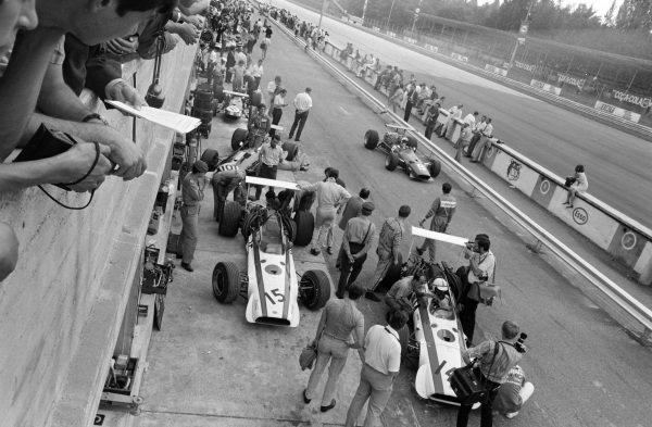 The Honda RA301s of David Hobbs and John Surtees at the end of the pit lane as Chris Amon, Ferrari 312, passes by.