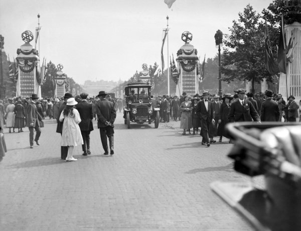 Crowds gather on the Mall as cars leave Buckingham Palace, during Peace Day celebrations in London.
