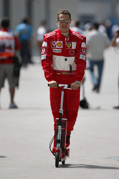 2004 United States Grand Prix - Friday Practice,Indianapolis, USA. 18th June 2004 Michael Schumacher, Ferrari F2004, enters the paddock on a motorised scooter.World Copyright: Steve Etherington/LAT Photographic ref: Digital Image Only